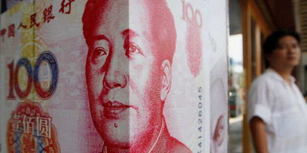 A man stands next to a copy of the Chinese RMB at a money exchange store in Hong Kong Friday, July 20,...