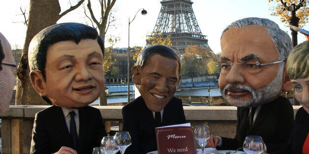 Oxfam activists wear masks from left, of French President Francois Hollande, Chinese President Xi Jinping,...