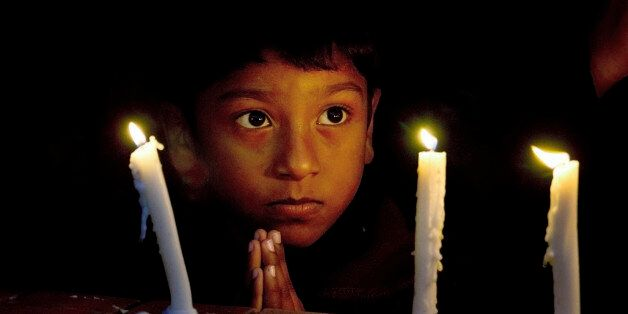 A Christian boy prays during a candlelight vigil for victims who were killed in Friday's attacks in Paris,...