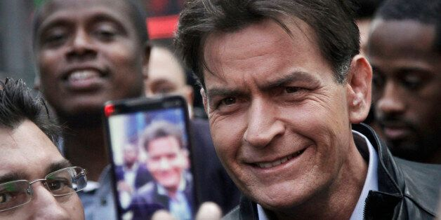 FILE - In this Monday, Jan. 14, 2013, file photo, actor Charlie Sheen is mobbed for autographs and photos...