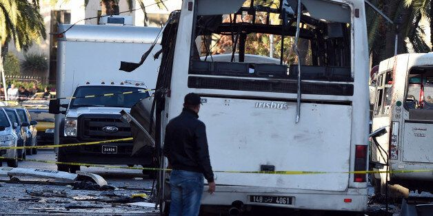 A plainclothes police officer walks beside the bus that exploded Tuesday in Tunis, Wednesday Nov.25,...