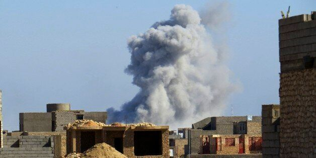 Smoke rises from Islamic State positions following a U.S.-led coalition airstrike during a military operation...