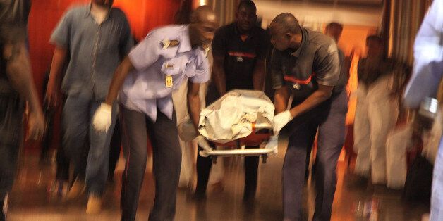Mali security personal carry the body of a victim inside the Radisson Blu hotel after an attack by gunmen...