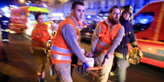 A woman is being evacuated from the Bataclan theater after a shooting in Paris, Friday Nov. 13, 2015....