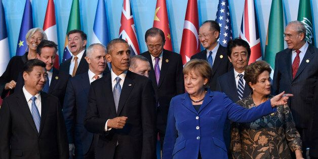 President Barack Obama, center, walks with Germany's Chancellor Angela Merkel, in blue, and other leaders...