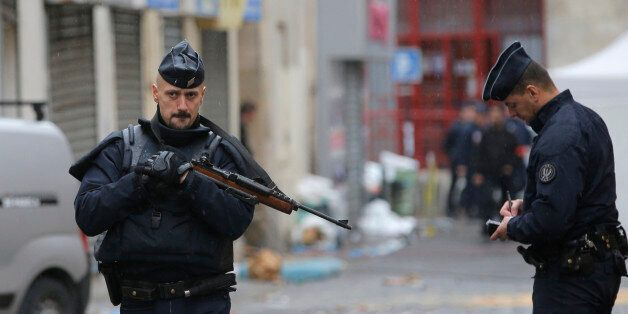 Police officers guard the street of Wednesday's raid on an apartment in Paris suburb Saint-Denis, Thursday...