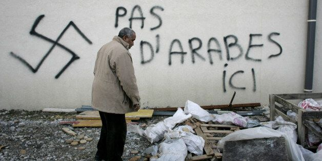 A Muslim resident stands by racial slurs painted on the walls of a mosque in the town of Saint-Etienne,...