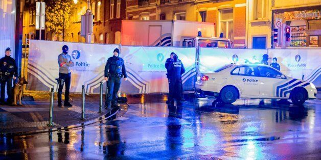 Belgian police guard a street in Brussels on Saturday, Nov. 14, 2015, where arrests were made linked...