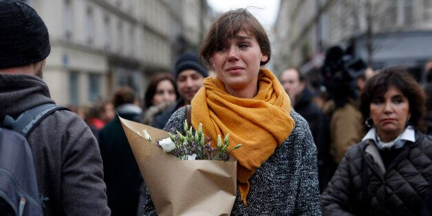 A woman carrying flowers cries in front of the Carillon cafe and the Petit Cambodge restaurant in Paris...