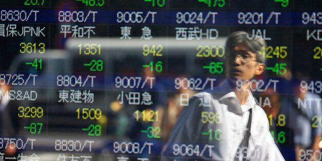 A man is reflected on an electronic stock indicator of a securities firm in Tokyo, Wednesday, Oct. 14,...