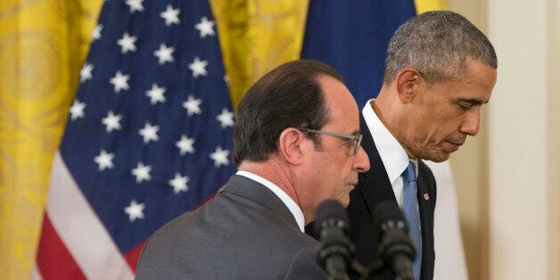 President Barack Obama and French President Francois Hollande walk off stage at the end of their news...
