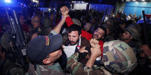 Lebanese soldiers arrest a suspected attacker attacker near the scene of a twin suicide attack in Burj...