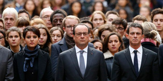 French President Francois Hollande, center, flanked by French Prime Minister Manuel Valls, right, and...