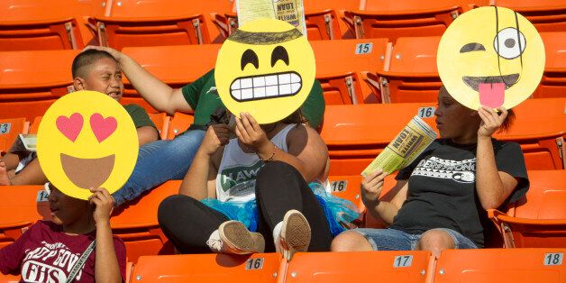 These Hawaii fans hold their emoji character mask in celebration of Halloween before the start of an...
