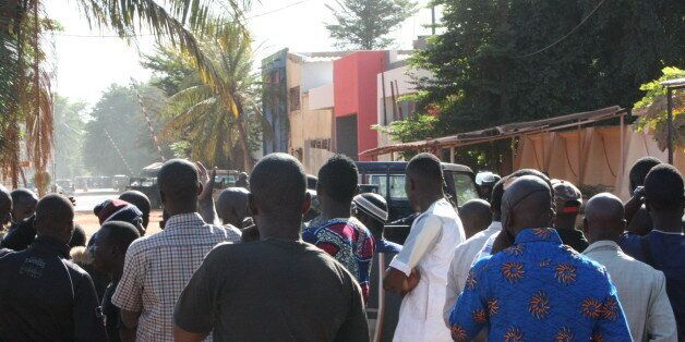 Onlookers gather near the Radisson Blu hotel after gunmen stormed the building in Bamako, Mali, Friday,...