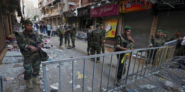 Lebanese army soldiers stand guard at the scene of Thursday's twin suicide bombings in Burj al-Barajneh,...