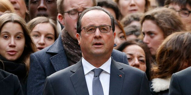 French President Francois Hollande stands among students during a minute of silence in the courtyard...