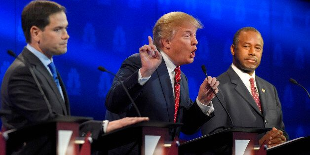Donald Trump, center, makes a point as Marco Rubio, left, and Ben Carson look on during the CNBC Republican...