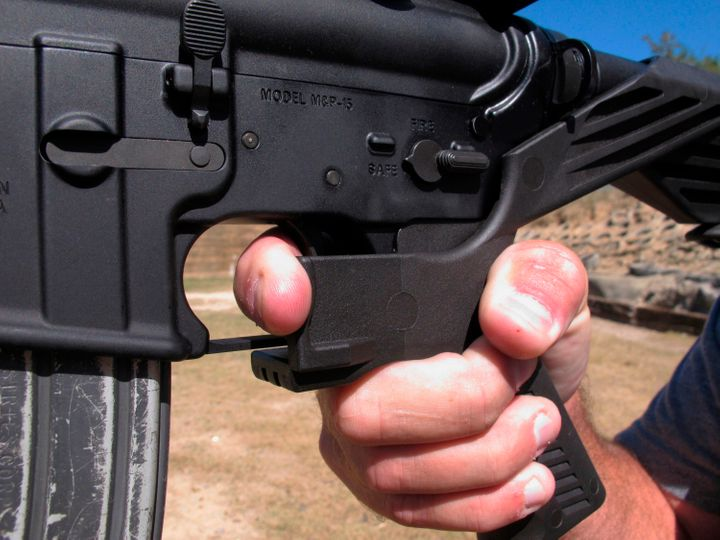 """In this Oct. 4, 2017 file photo, a shooting instructor demonstrates the grip on an AR-15 rifle fitted with a """"bump stock"""" at"""