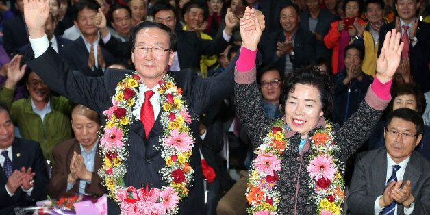 28일 열린 재보선 선거에서 경남 고성 군수로 당선된 새누리당 최평호 후보가 선거사무실에서 부인 이화순씨와 환호하고