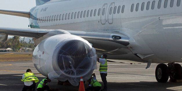 Workers cover a plane engine with a plastic sheet in their attempt not to be damaged by volcanic ash...