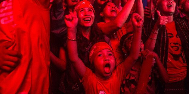 YANGON, MYANMAR - NOVEMBER 09: A child stands with crowds gathered for the election result announcement...