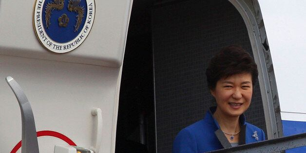 South Korean President Park Geun-hye smiles from her plane upon arrival at Bali airport, Indonesia, Sunday,...