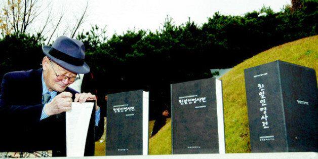지난 2009년 11월 8일 서울 용산구 효창동 백범 김구 묘소에서 열린 '친일인명사전 발간 국민보고대회'에서 한 시민이 백범의 제단에 바쳐진 사전을 살펴보고