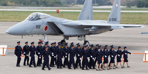 Japan Self-Defense Force (SDF) members walk in front of F-15 J/DJ Fighter during the annual Self-Defense...
