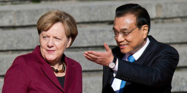 Chinese Premier Li Keqiang, right, shows the way for German Chancellor Angela Merkel during a welcome...