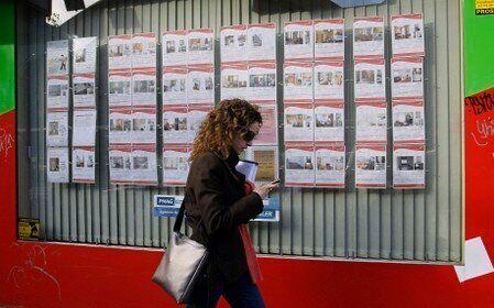Una joven pasa por delante de una agencia inmobiliaria con anuncios de casas en alquiler o en venta en...