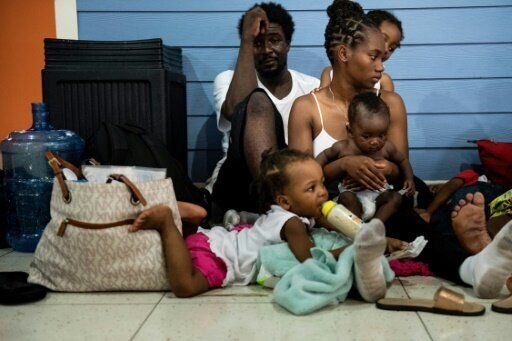 Ronald Samuel and his wife, Kimberley Samuel, shelter with their children at Marsh Harbor airport in...