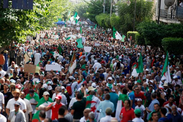 Protesters chant slogans as they march with Algerian national flags and anti-establishment signs during...