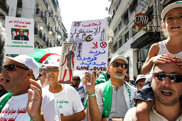 A protester raises up a sign reading in Arabic