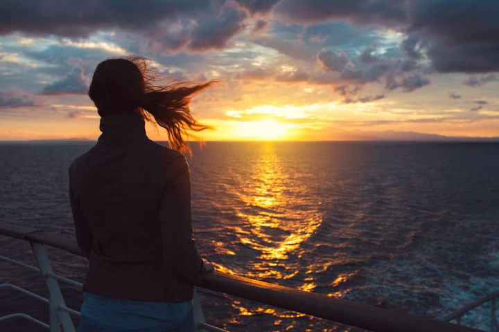 Rear view of a young woman standing by the fence of a sailing ship and enjoying the sunset view.