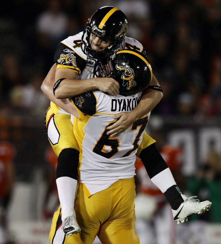 Peter Dyakowski lifts kicker Sandro DeAngelis after a field goal against the B.C. Lions in Vancouver on Sept. 18, 2010.