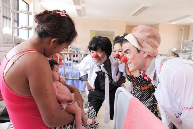 Doutores da Alegria tentam animar criança internada em hospital público.