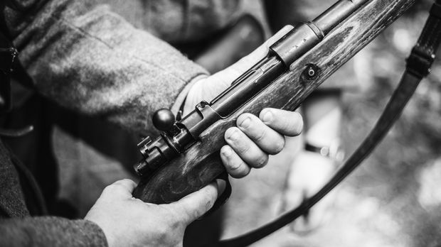 Re-enactor Dressed As World War II German Soldier Holding Rifle. Photo In Black And White Colors. Soldier Holding Weapon. German Military Ammunition Of A German WW2 Soldier.
