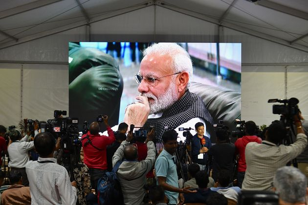 Prime Minister Narendra Modi is seen on a tv screen as he watches the live broadcast of the soft landing...
