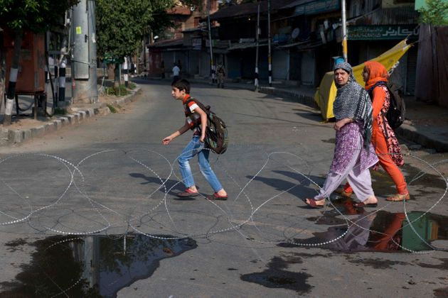 Kashmiri children accompanied by their mother walk past barbwire setup as road blockade by Indian paramilitary...