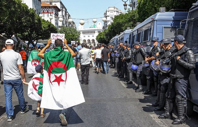 Protesters draped in Algerian national flags walk past riot police members and vehicles along a street...
