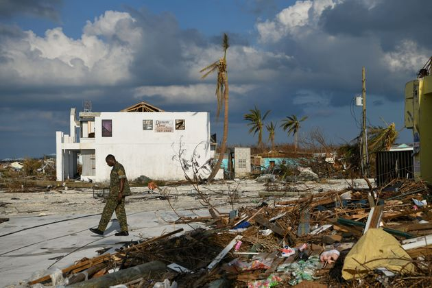 A member of the Bahamian military assesses damage in a destroyed neighborhood in the wake of Hurricane...