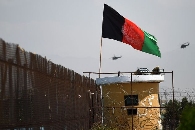 Two US military helicopters are seen flying past an Afghan national flag during the 100th anniversary...