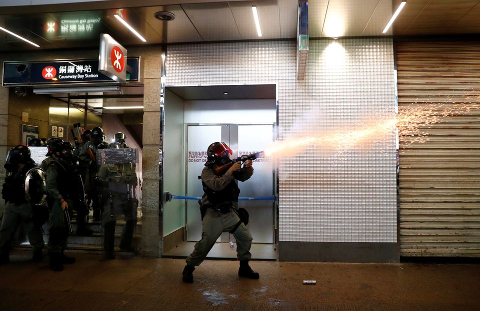 A riot police officer fires a tear gas canister during a rally in Central, Hong Kong, China September...