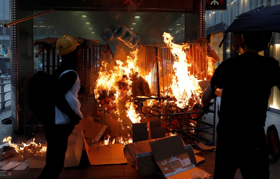 Protestors stand next to a fire at the entrance of MTR Central Station in Hong Kong, China September...