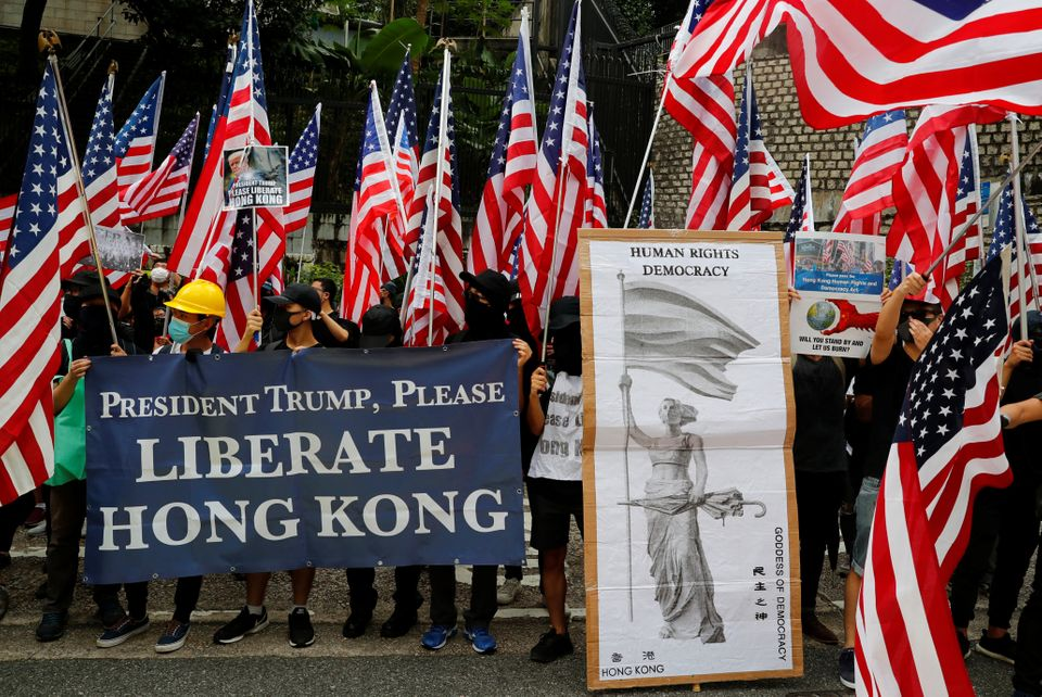 Protesters hold signs and U.S. flags during a rally in Hong Kong, China September 8, 2019. REUTERS/Anushree