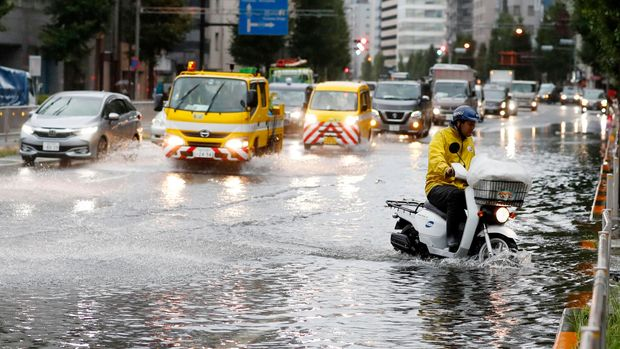 A man rides a moped through a flooded street due to a typhoon in Tokyo Monday September 9, 2019. (Kyodo News via AP)