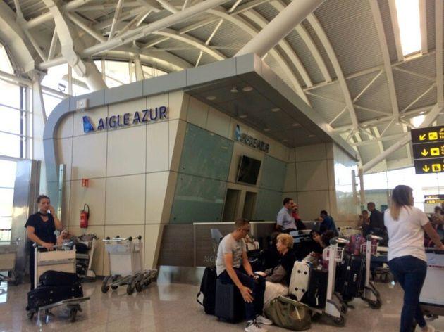 Des passagers attendent dans la zone d'embarquement de la compagnie aérienne française Aigle Azur...