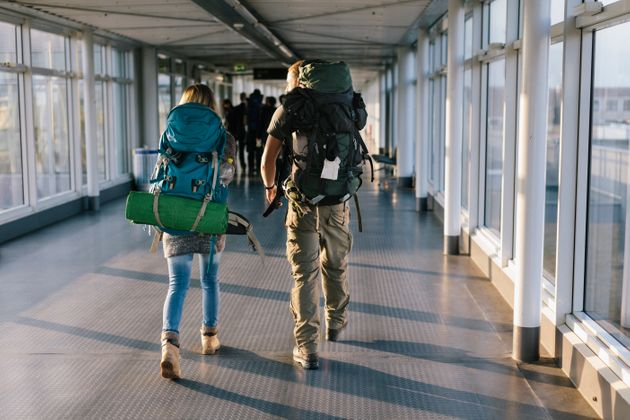 Young backpacking couple walking towards boarding