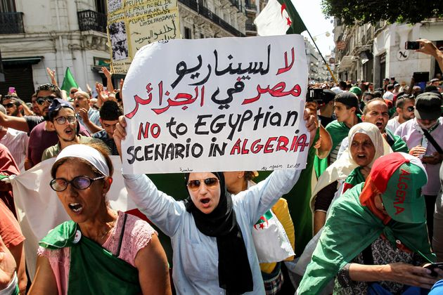 A protester raises up a sign reading in Arabic and English
